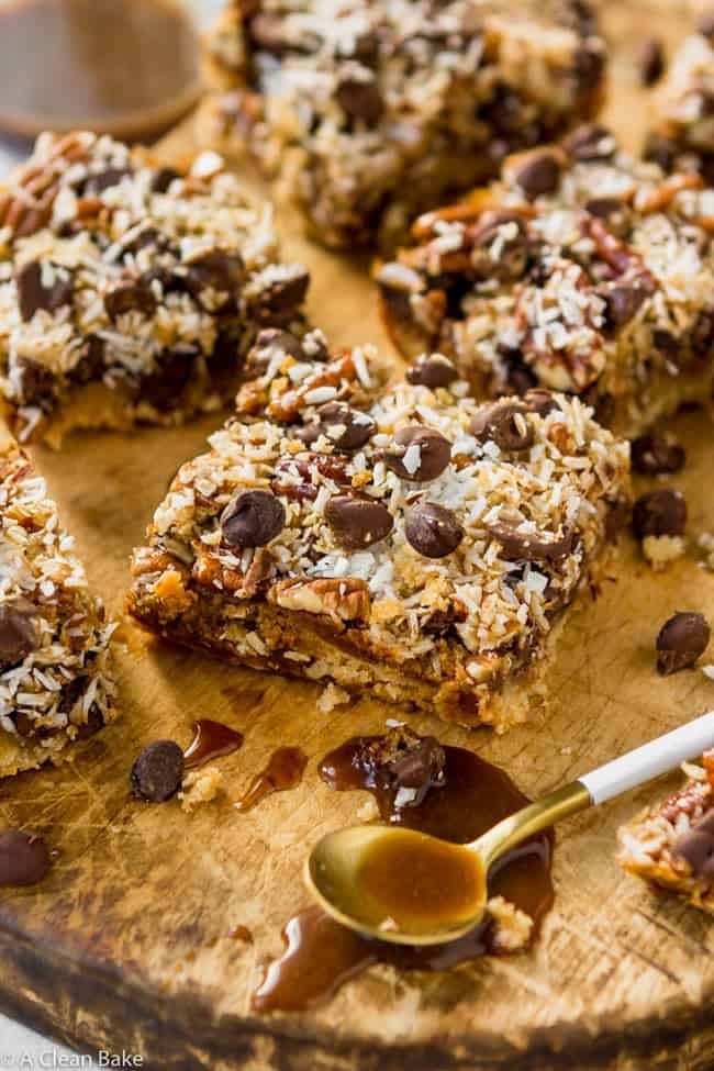 Magic cookie bars on a wood cutting board topped with coconut flakes