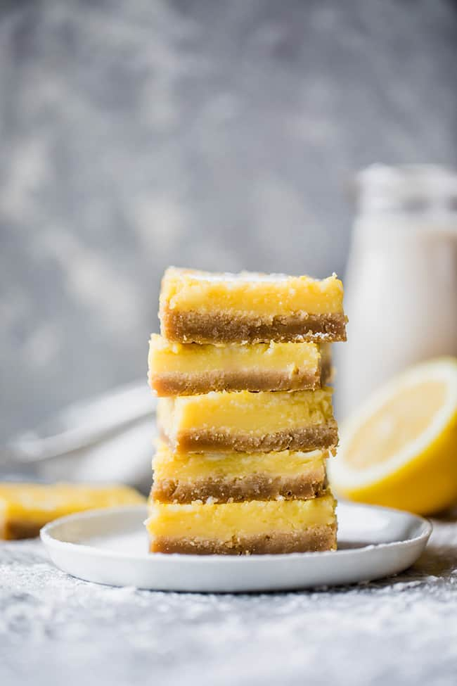 Stack of 5 healthy lemon bars on a plate with powdered sugar on top