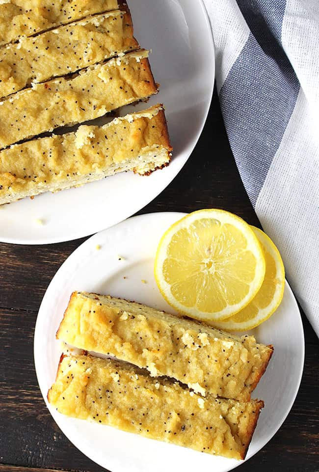 Slices of lemon poppy seed bread on a plate with lemon slices. Loaf at top right.