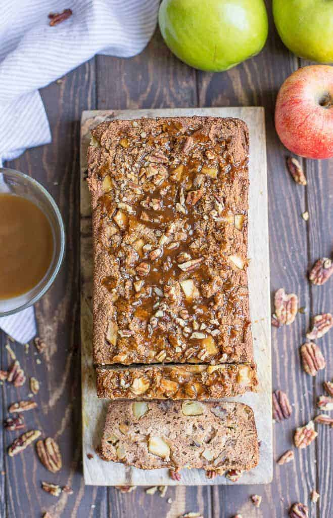 Loaf of caramel apple bread with two slices cut, nuts and apple around.