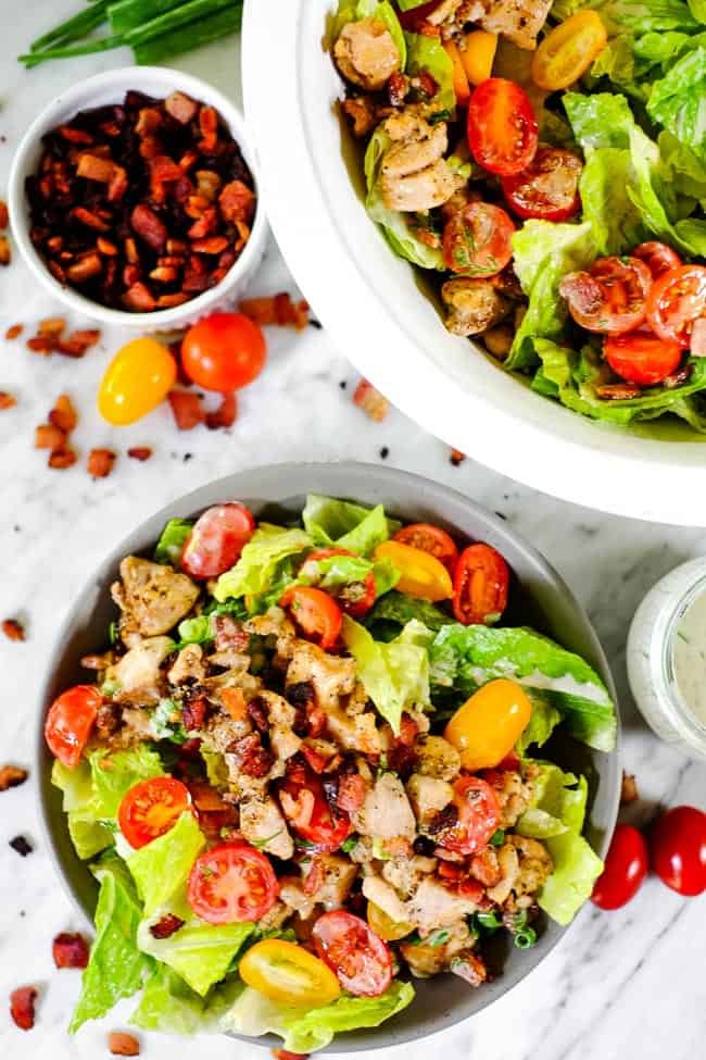 BLT salad in a bowl with larger serving bowl, extra bacon, tomatoes and dressing on the side.