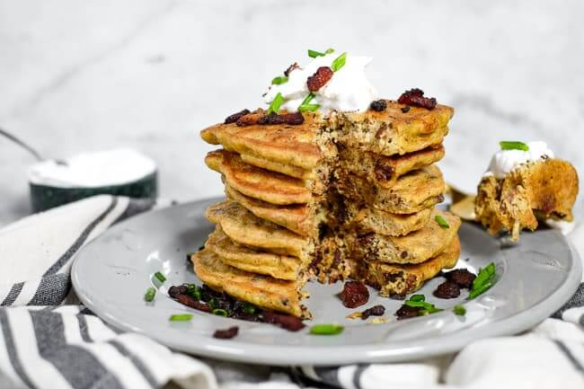 Bacon pancakes in a stack on a plate with coconut yogurt on top. Garnished with bacon bits and chives.