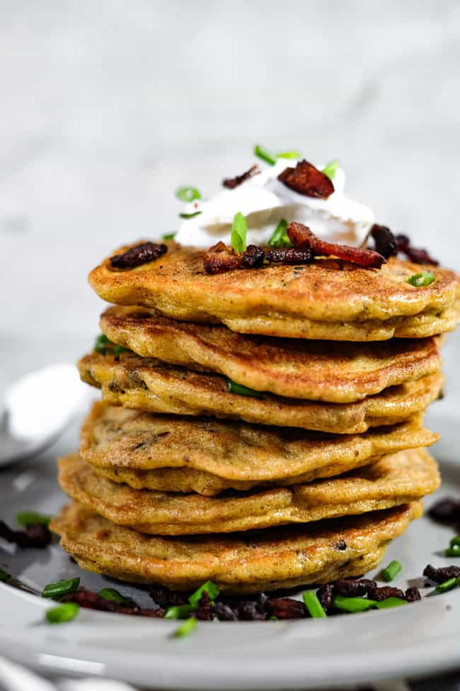 Close up of bacon pancakes in a large stack on a plate. Topped with coconut yogurt, bacon bits and chives.
