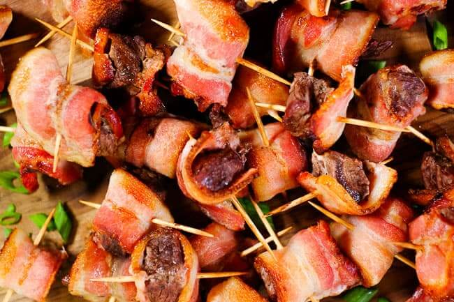 Bacon wrapped steak bites piled on a cutting board with chopped green onion garnish.