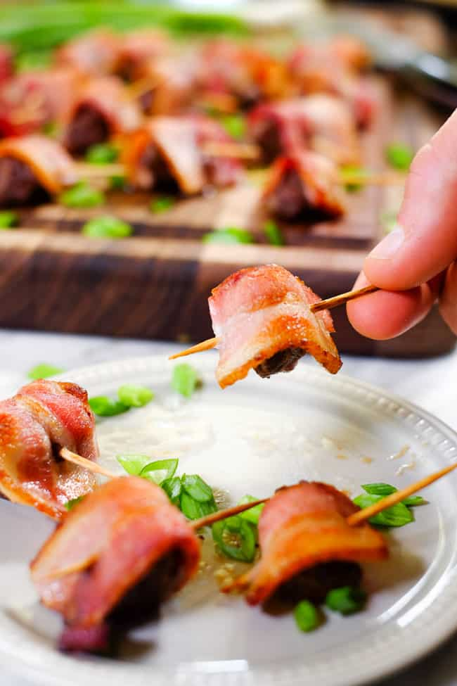 Bacon wrapped steak bites on a plate with one being held up.