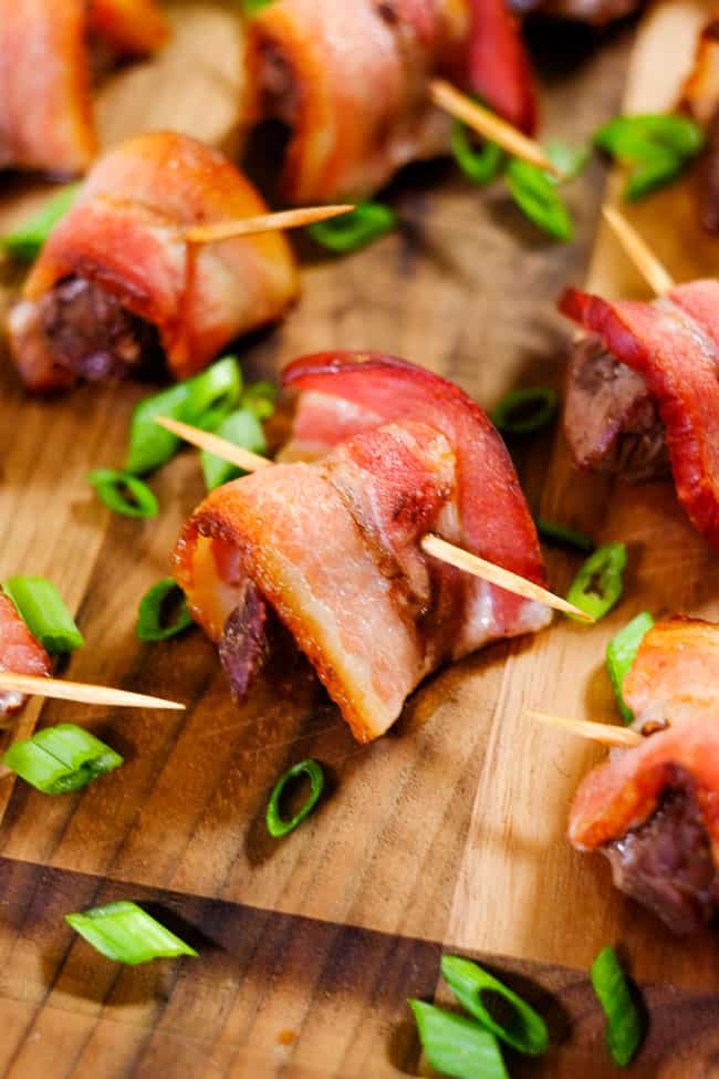 Close up of bacon wrapped steak bites on cutting board with chopped green onion.