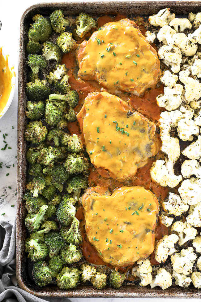 Honey mustard pork chops on a sheet pan with broccoli and cauliflower.