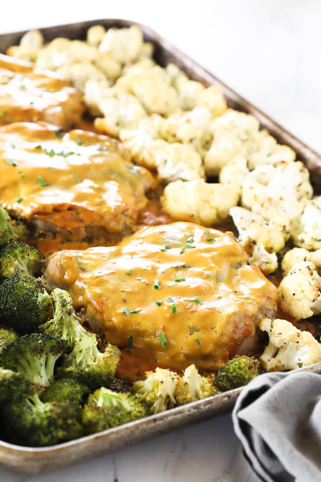 Angled image of honey mustard pork chops on a sheet pan with broccoli and cauliflower.