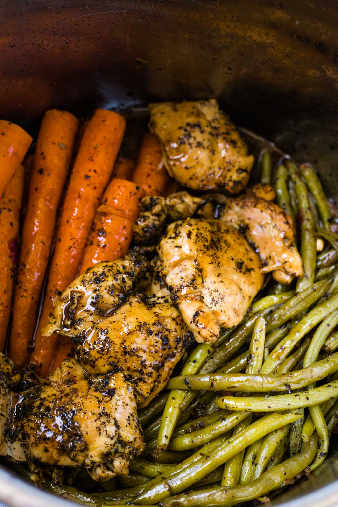 Instant pot full of cooked chicken thighs, carrots and green beans