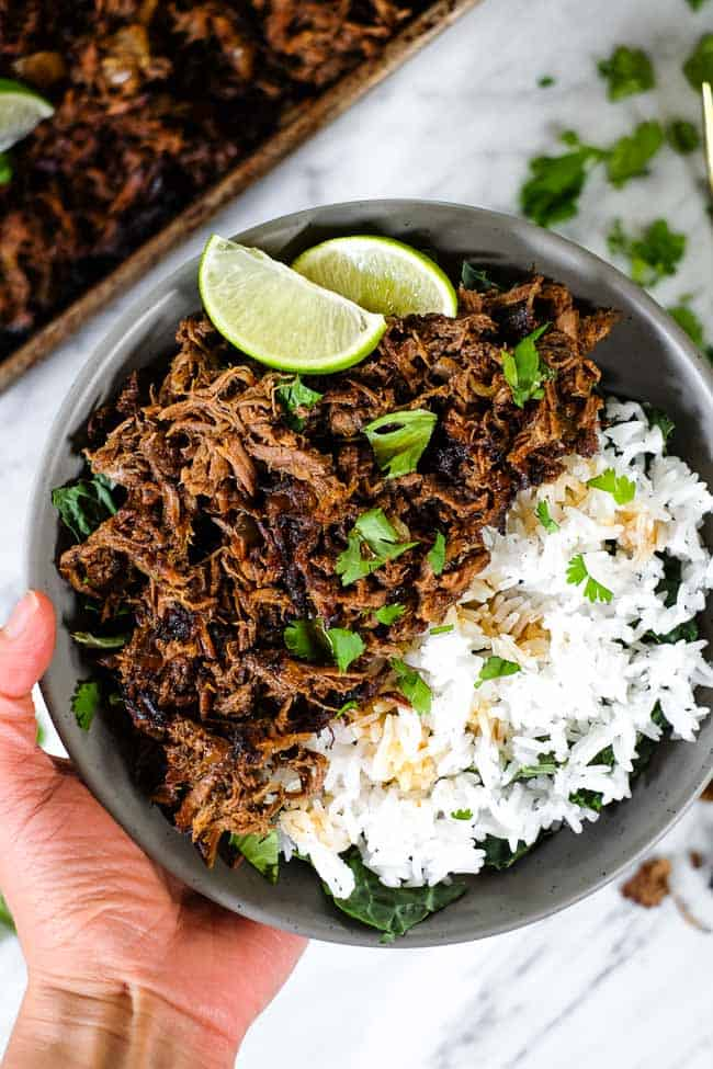 Beef barbacoa in a bowl with greens and rice and topped with chopped cilantro and lime wedges.