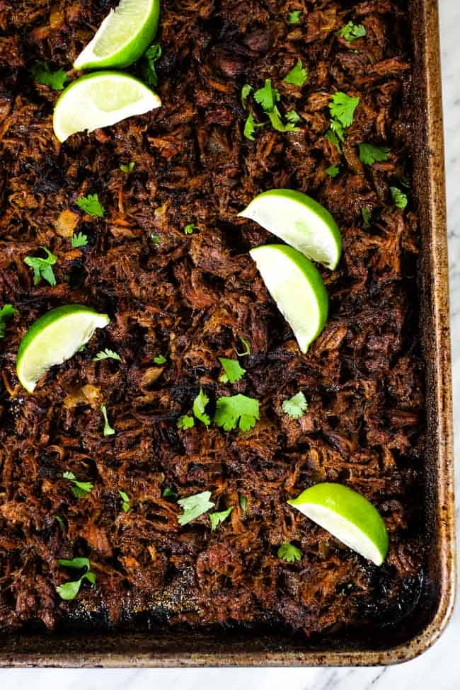 Beef barbacoa on a sheet pan topped with chopped cilantro and lime wedges.