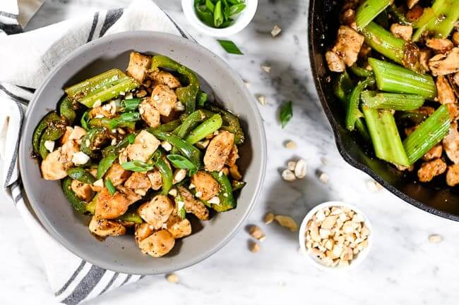 Black pepper chicken with bell pepper and celery served in a bowl and garnished with chopped green onion and cashews.