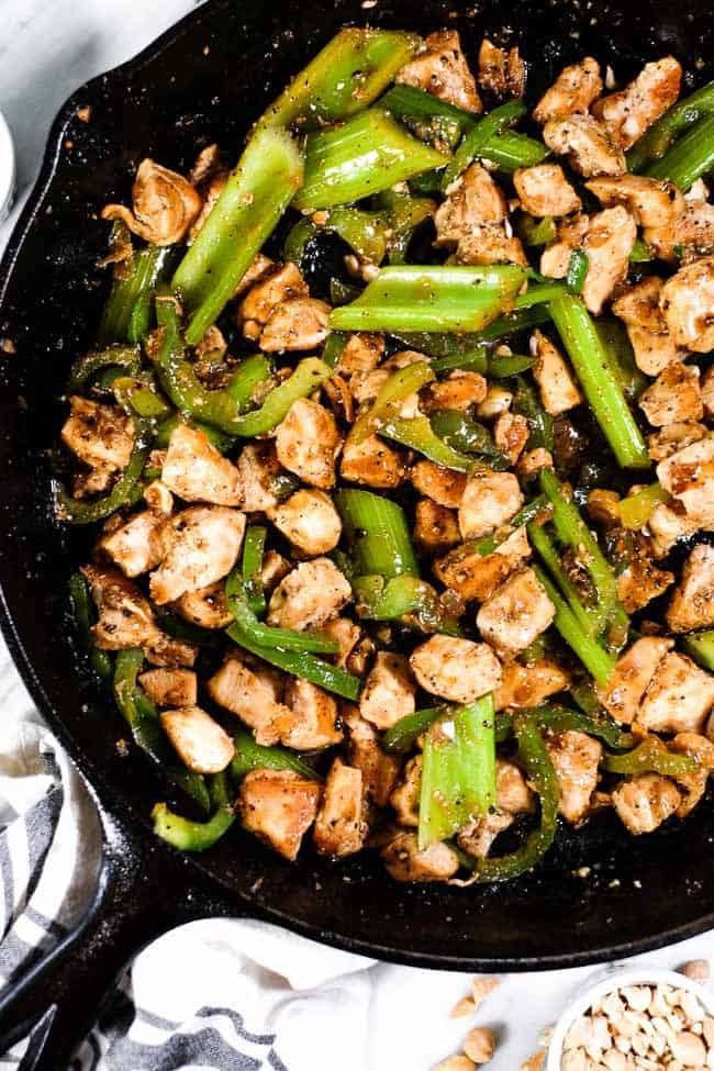 Black pepper chicken with bell pepper and celery in a cast iron skillet.