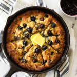 Blueberry cornbread in a skillet with blueberry sauce on the side and grass fed butter melting on top.