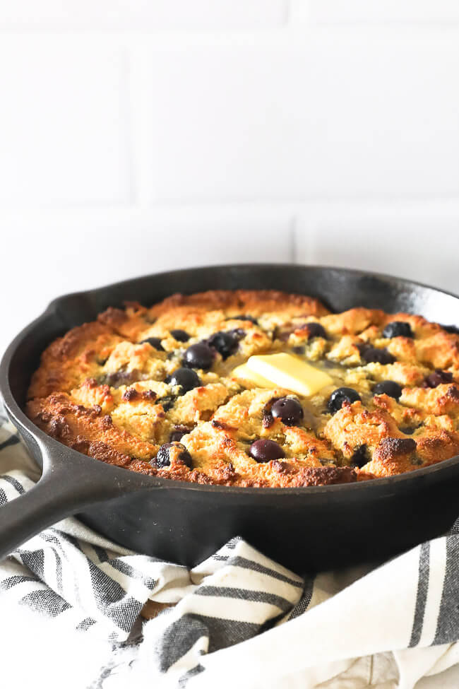Vertical angled shot of blueberry cornbread in a cast iron skillet. Cut up into pieces with grass fed butter melting on top.