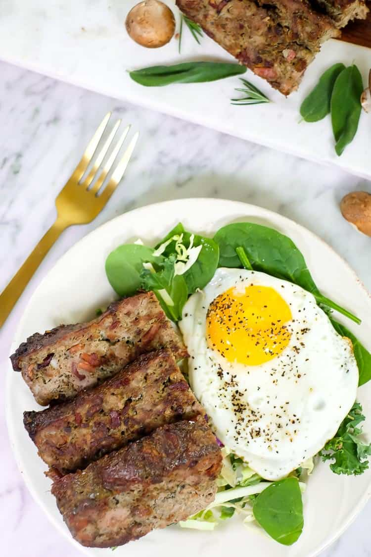 Breakfast meatloaf with bacon vertical overhead with egg and fork