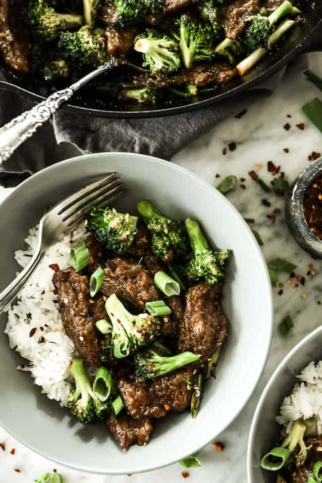 Broccoli beef stir fry served in a bowl with white rice and topped with chopped green onion and crushed red pepper.