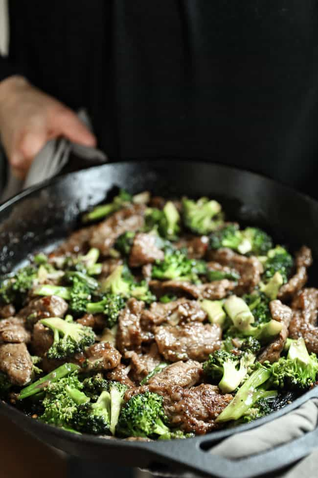 Holding a cast iron skillet with broccoli beef stir fry in it.