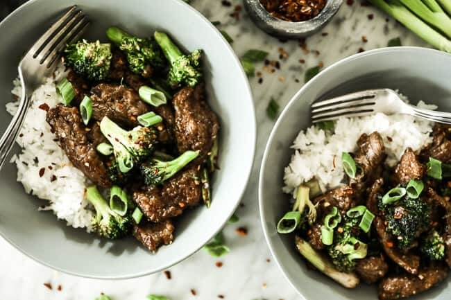 Broccoli beef stir fry served up in two bowls with white rice, crushed red pepper sprinkled on top and forks in the bowls.