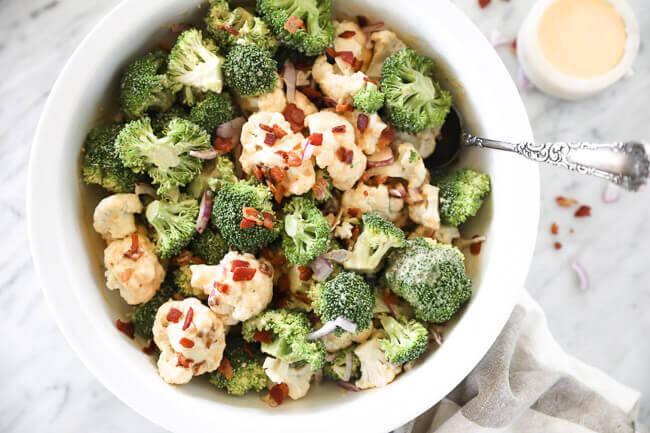 Broccoli and cauliflower florets with bacon and red onion sprinkled on top horizontal image