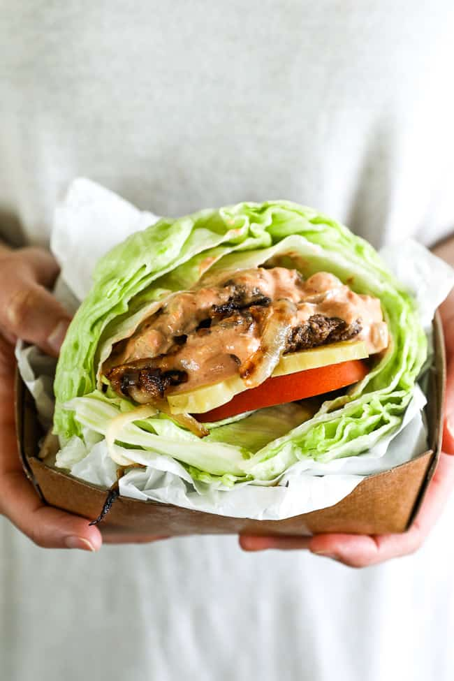 Hands holding a burger wrapped in a lettuce bun with sauce