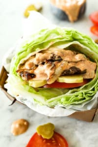 Keto bunless burger with lettuce bun and special sauce slathered over patties