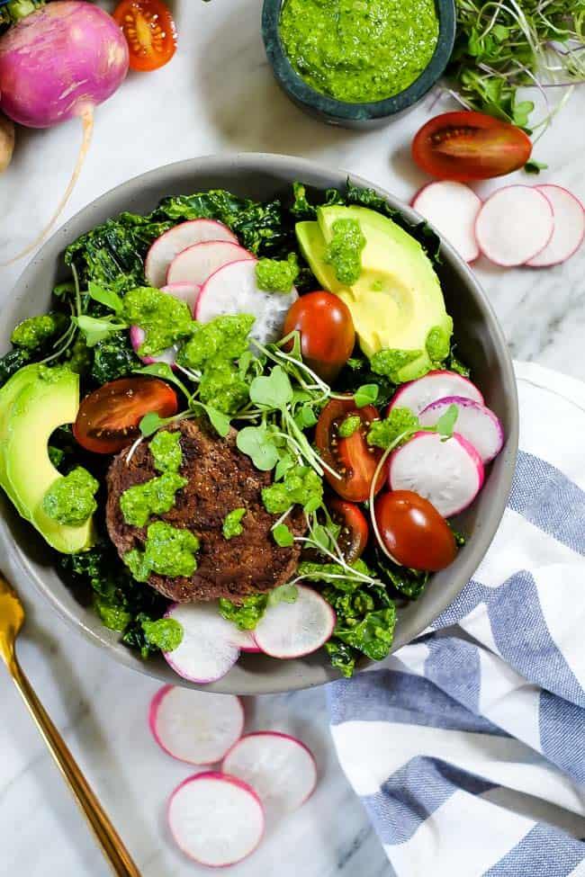 Burger salad bowl with pesto, kale, radish, tomatoes, avocado and micro greens.