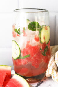Tall glass filled with watermelon cucumber mojito mocktail