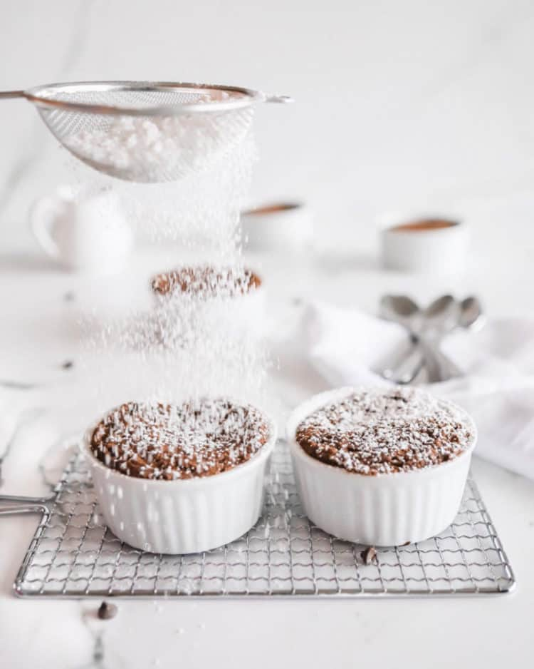Mug cakes with powdered sugar being dusted on top.