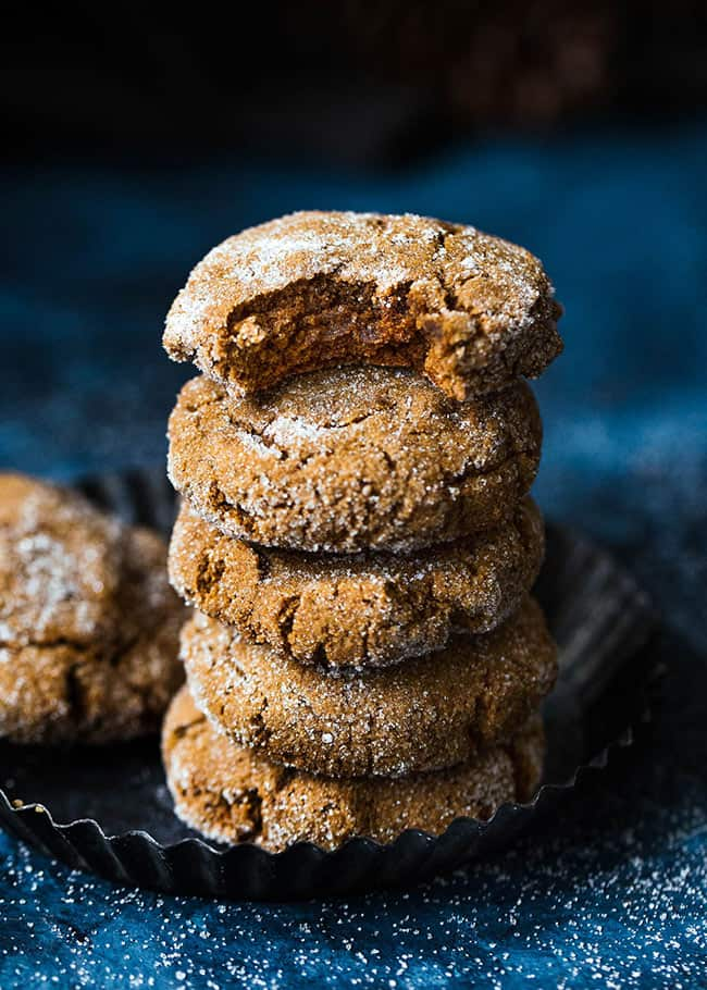 Stack of ginger molasses cookies, top cookie with bite taken out