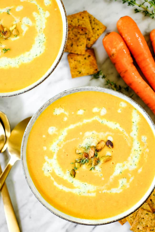 Carrot ginger soup in two bowls with tzatziki sauce, pistachios and fresh thyme. On a table with extra sauce, thyme, crackers and carrots.