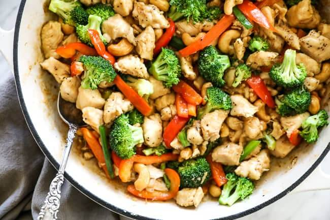 Overhead image of cashew chicken in a skillet with a serving spoon dipped in. Chicken, cashews, broccoli, red bell pepper and an asian sauce.