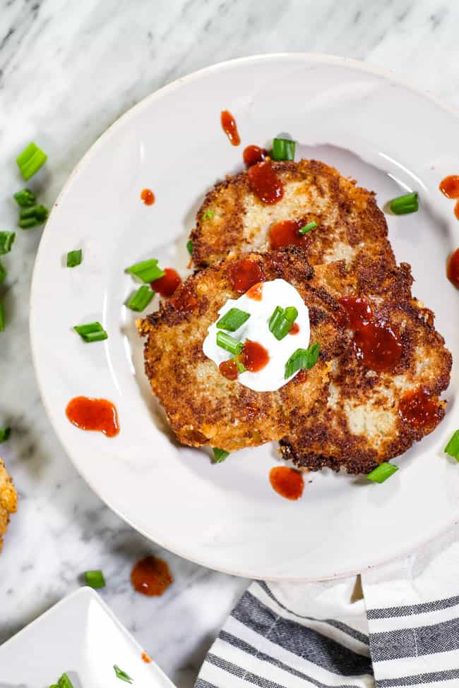 Cauliflower fritters on a plate topped with hot sauce, coconut yogurt and chopped green onion.