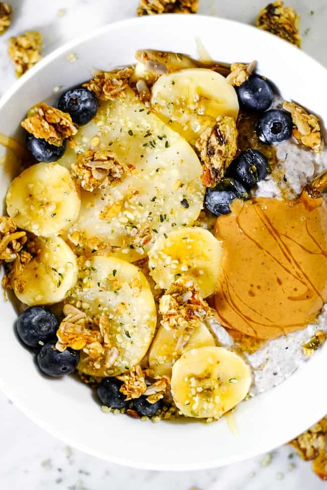 Chai spiced paleo chia seed pudding with sliced bananas, pears, blueberries, grain free granola and nut butter.