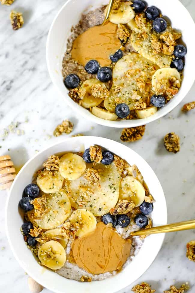 Two bowls of chai spiced paleo chia seed pudding with sliced bananas, pears, blueberries, grain free granola and nut butter.