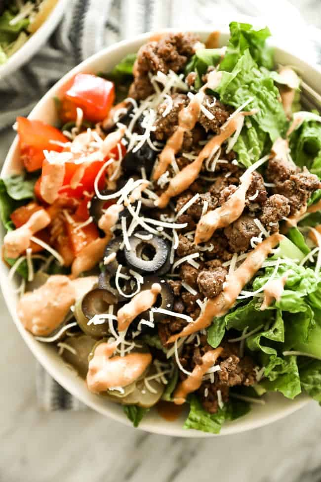 cheeseburger salad in a bowl with shredded cheese on top and special sauce drizzled over the top.