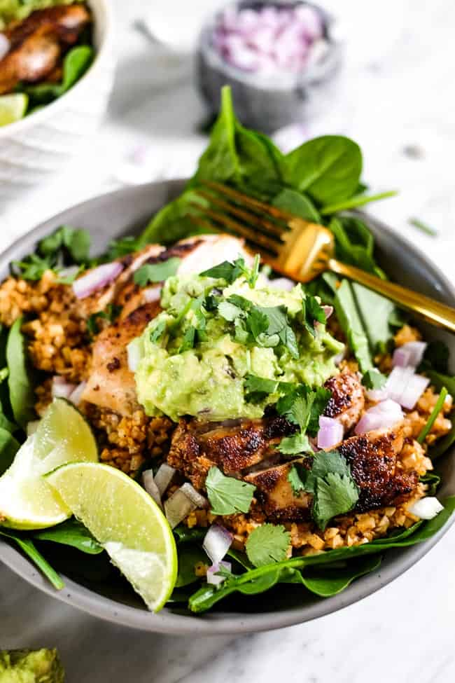 Angled shot of chicken burrito bowl, topped with chopped red onion, guacamole, cilantro and lime wedges.