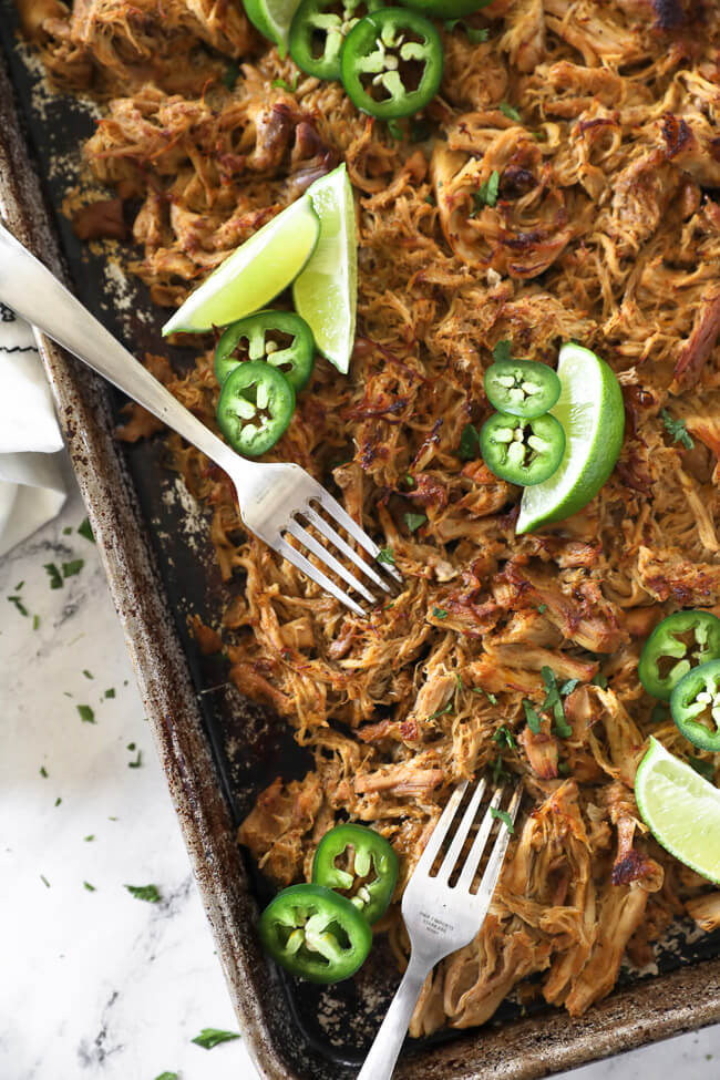 Overhead vertical image of crispy chicken carnitas on a sheet pan with two forks for shredding, lime wedges, sliced jalapeño and chopped cilantro.