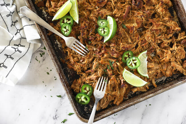 Overhead horizontal image of crispy, shredded chicken carnitas on a sheet pan with two forks, lime wedges, jalapeño slices and fresh chopped cilantro.