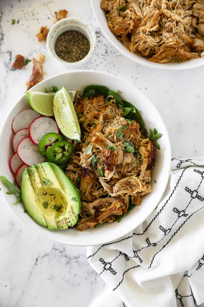 Overhead vertical image of chicken carnitas served in a bowl with greens, sliced radish, lemon wedges, sliced jalapeño and avocado slices. Topped with chopped cilantro.