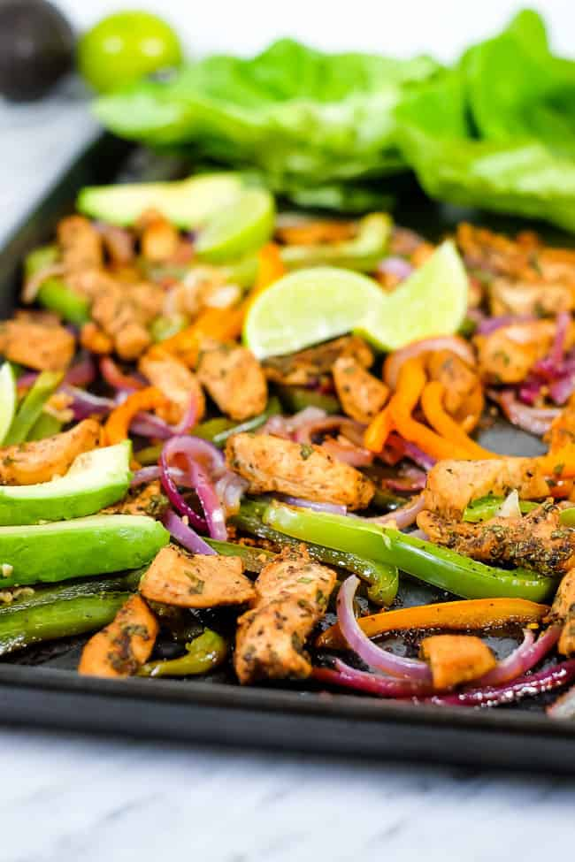 Sheet pan chicken fajita bake with avocado, lime, cilantro and butter lettuce on sheet pan.