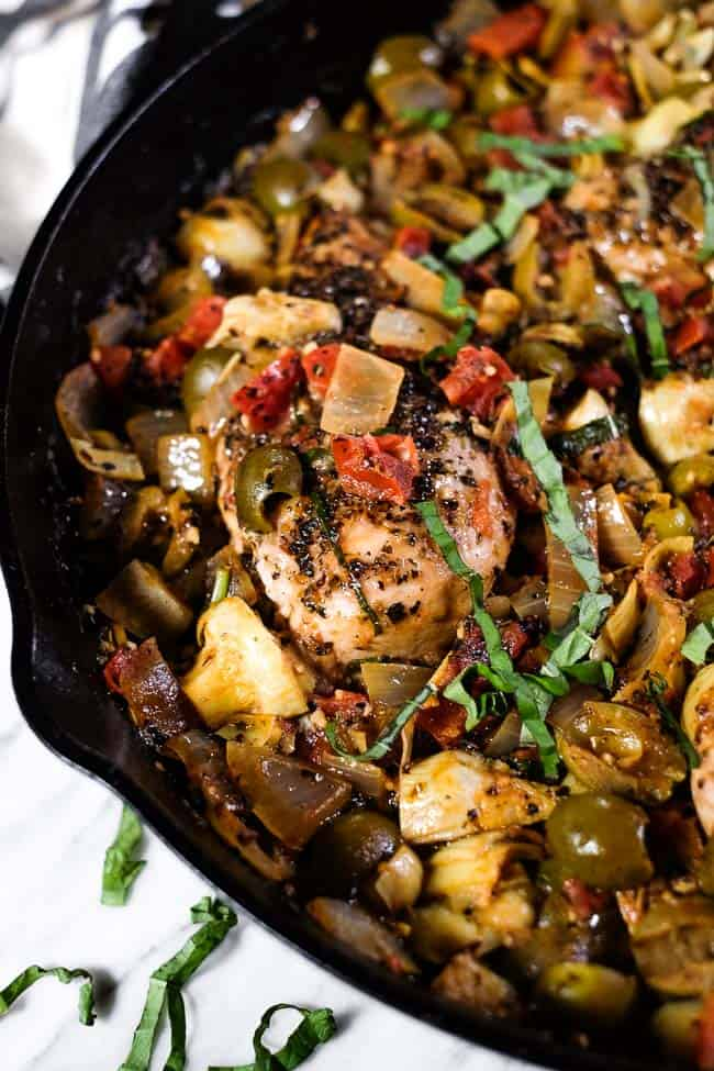 Chicken in tomato sauce in a large skillet with fresh basil on top.