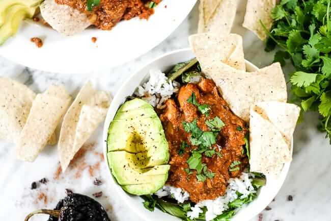 Chicken mole recipe in a bowl with greens, rice, avocado and grain free tortilla chips. Topped with chopped cilantro.