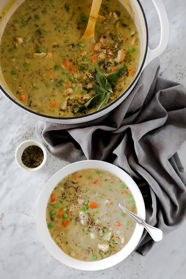 Vertical image of chicken pot pie soup served in a bowl with a spoon in it. Large soup pot in the image as well with ground pepper on the side.