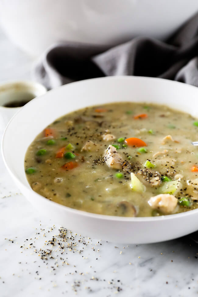 Vertical angled image of a bowl of chicken pot pie soup with extra ground pepper sprinkled on top.