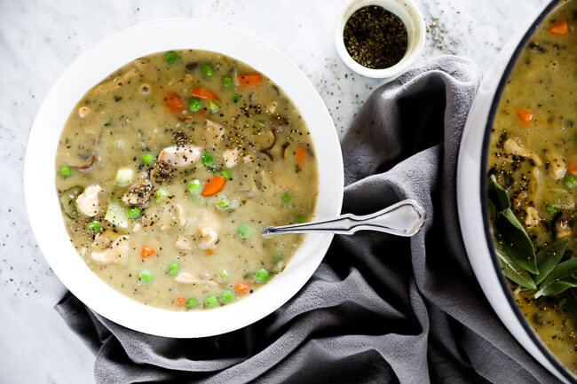 Horizontal image of chicken pot pie soup served in a bowl with a spoon and extra pepper sprinkled on top.