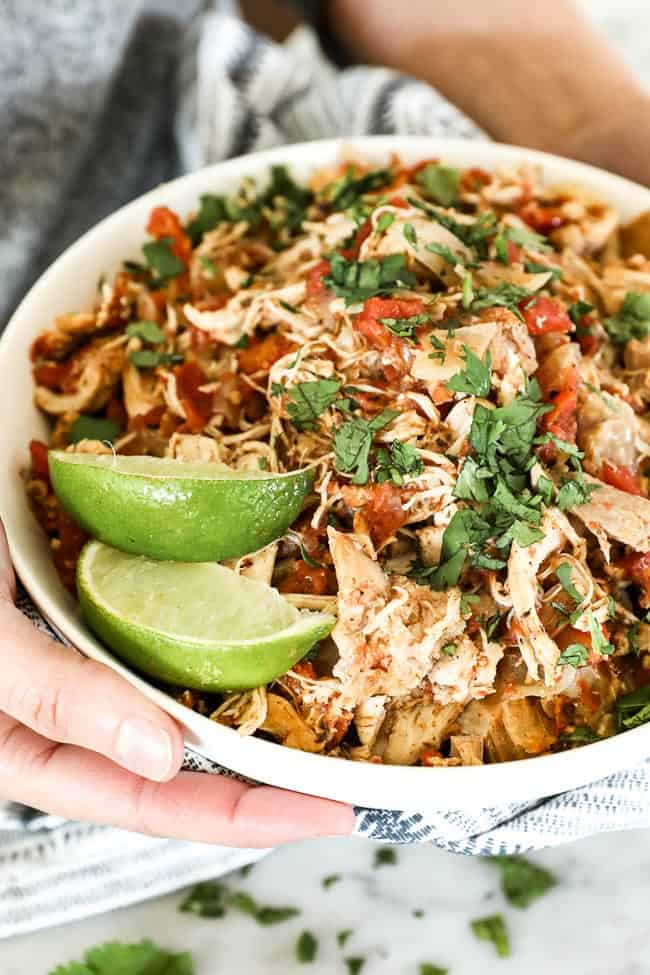 Holding a bowl of shredded chicken with cilantro and lime wedges.