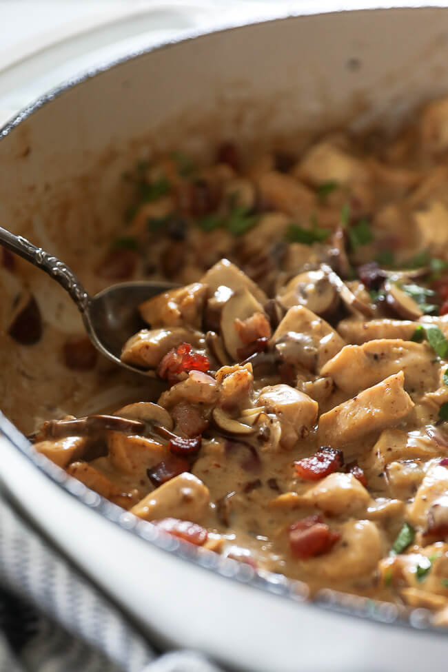 Angled shot of chicken with creamy mushroom sauce in a skillet with a serving spoon scooping some up.