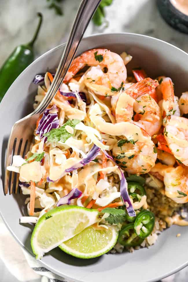 Close up shot of cilantro lime shrimp bowl with fork in it, topped with sauce, jalapeño slices and lime wedges.