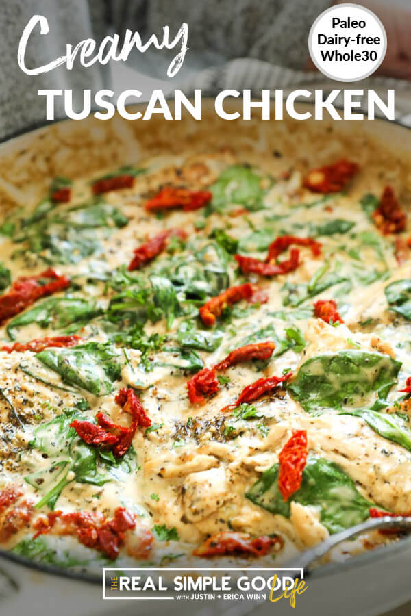 Close up angle of creamy tuscan chicken in a pan with spinach and sun dried tomatoes. Text at top.
